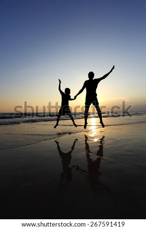 Father and son  fun jumping on the beach at the sunset time