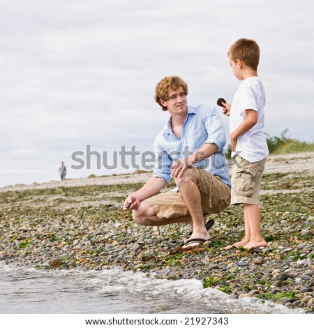 Father and son gathering rocks at beach - stock photo