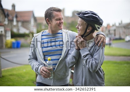 Father and Son getting ready for their bike ride. The father has his arm around his son and they are smiling at each other.  - stock photo