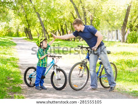 father and son give high five while cycling in the park - stock photo