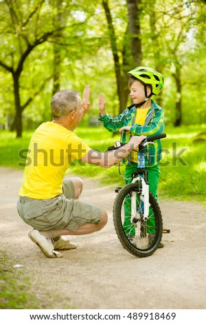 Father and son give high five while cycling in the park