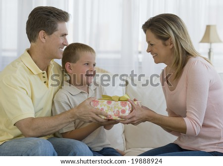 Father and son giving a gift to mother - stock photo