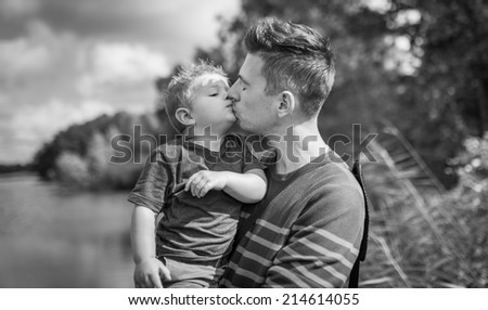 father and son giving each other a kiss in black and white - stock photo