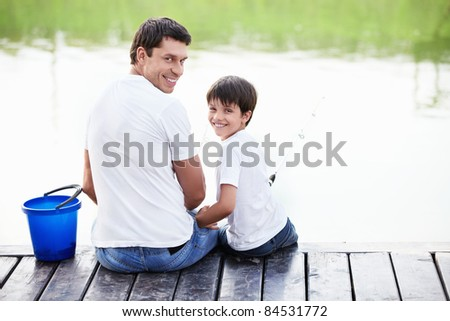 Father and son go fishing with fishing poles - stock photo