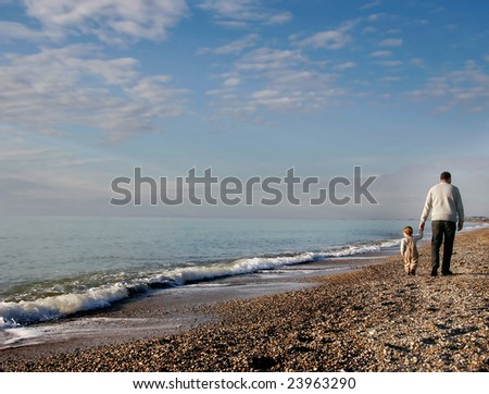 father and son going away on pebble beach - stock photo