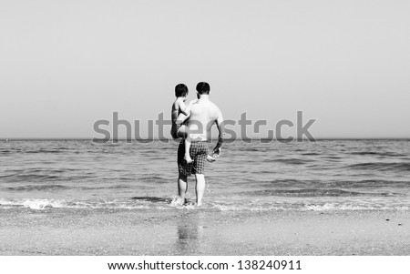 father and son going to swim in the sea. black and white photo.