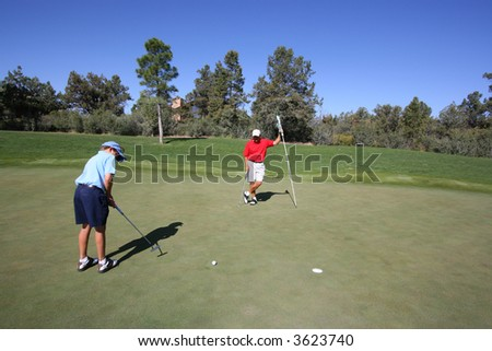 Father and son golfing where son is putting and father is holding the flag