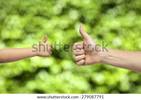 father and son hands giving like on natural green background - stock photo