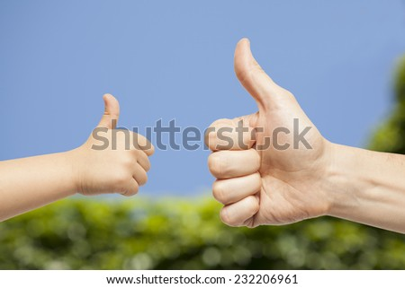 father and son hands giving like on nature background - stock photo