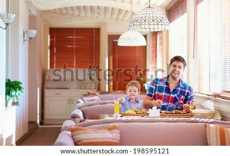 father and son have a dinner in restaurant - stock photo