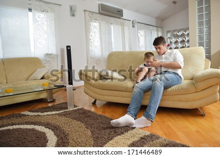 father and son have fun play games and have education lessons on tablet computer at home - stock photo