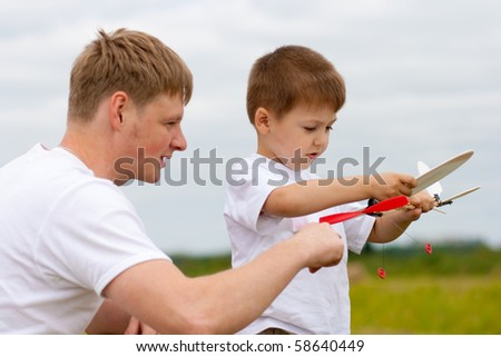 Father and son have fun with toy aircraft model in park - stock photo