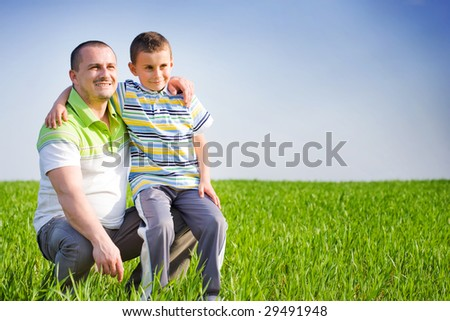Father and son having a good time outdoor in wheat field