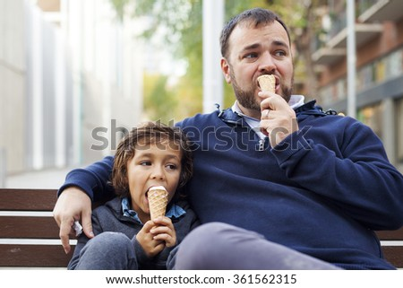 father and son having a ice cream on a bench in the street, family and parenthood - stock photo
