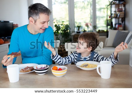 Father and son having breakfast at home