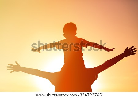 father and son having fun at sunset sky - stock photo