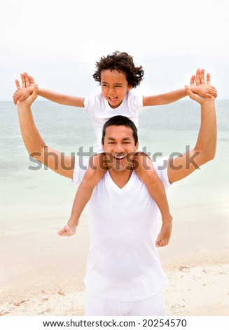 father and son having fun at the beach - stock photo
