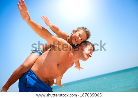 Father and Son having fun at the beach. Travel and Vacation concept. Happy Dad with Little Child Having Fun outdoors. Joyful Family. Summer Holidays