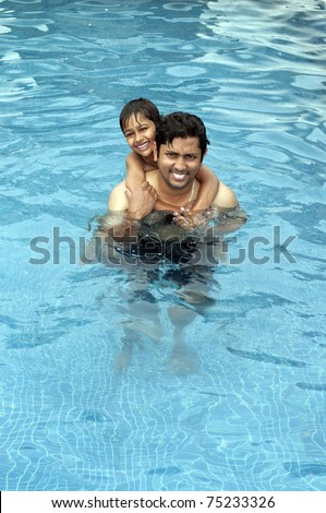 Father and Son having fun at  the resport pool - stock photo