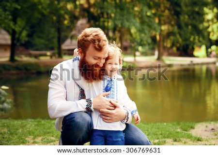 Father and son having fun in a park in a traditional white shirts with ornament. - stock photo