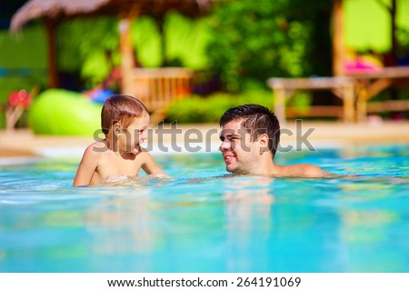 father and son having fun in outdoor pool, summer vacation - stock photo