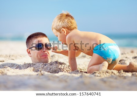 father and son having fun in sand on the beach - stock photo