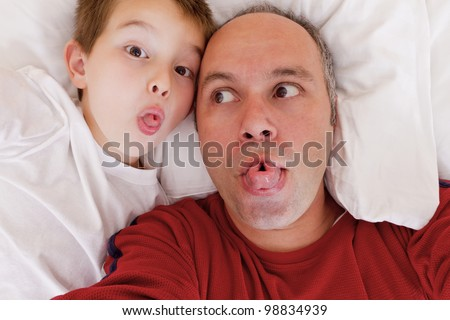 Father and son having fun in the bed by rolling their tongues. - stock photo