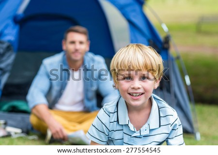 Father and son having fun in the park on a sunny day - stock photo