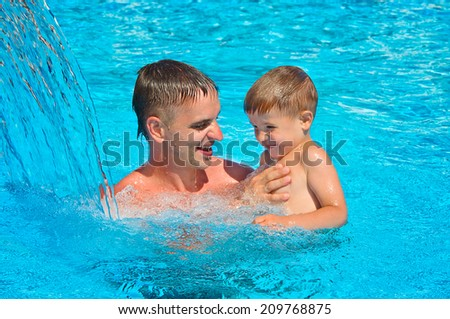 Father and son having fun in the pool
