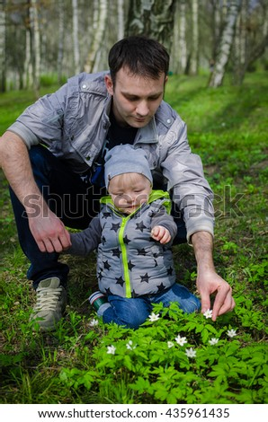 Father and son having fun in the spring park collecting flowers.  Father's day. Toddler and father have fun outside. Father's Day. Happy Fathers Day. Happy family. Father and baby. - stock photo