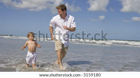 Father and son having fun on a beach