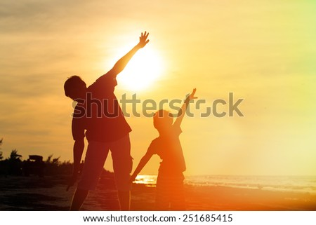father and son having fun on sunset beach - stock photo