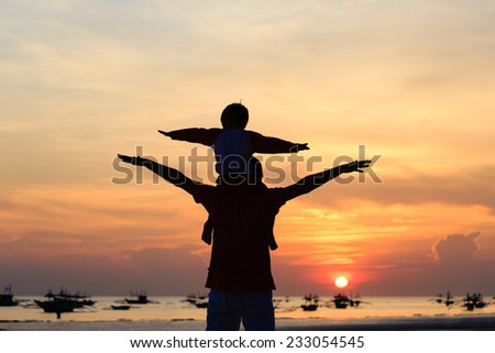 father and son having fun on sunset tropical beach - stock photo
