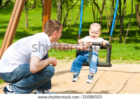 Father and son having fun on the playground - stock photo