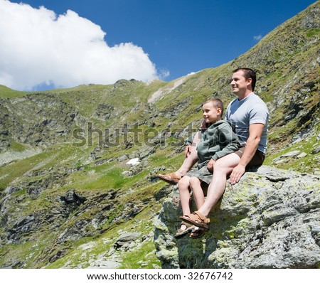 Father and son having fun outdoor in the mountains - stock photo