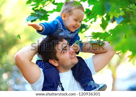 father and son having fun playing outdoors - stock photo