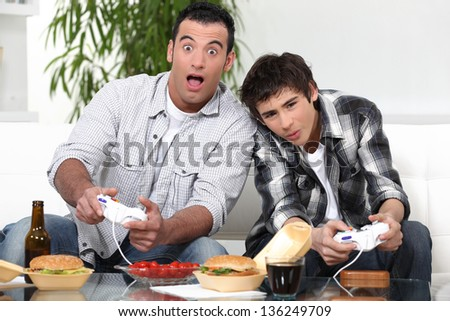 Father and son having fun playing video games - stock photo