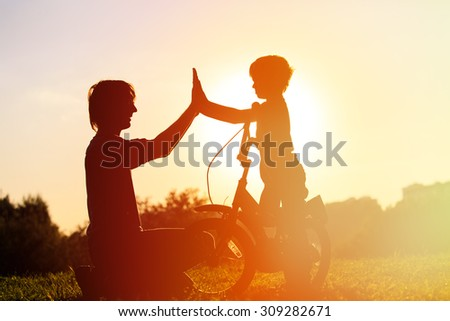 father and son having fun riding bike at sunset, active kids sport - stock photo