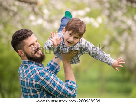 Father and son having fun together in summer park.