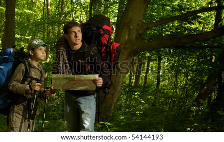 Father and son hiking in forest. Looking at map. - stock photo