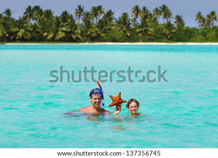 Father and son holding a starfish on a tropical beach