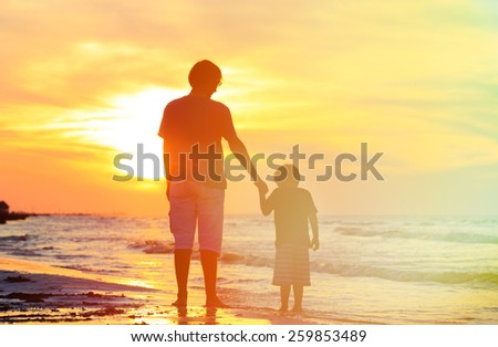 father and son holding hands at sunset sea