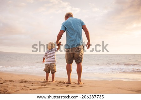 Father and son holding hands walking on the beach at sunset - stock photo