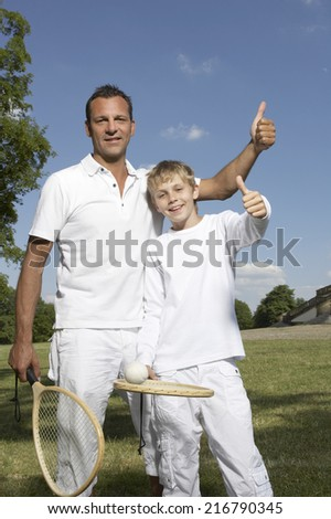 Father and son holding tennis rackets. - stock photo