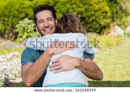 Father and son hugging in the countryside - stock photo