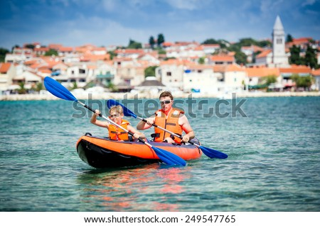 father and son in a kayak - stock photo