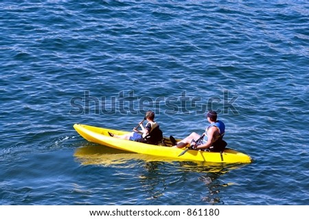 Father and son in an ocean going kayak - stock photo