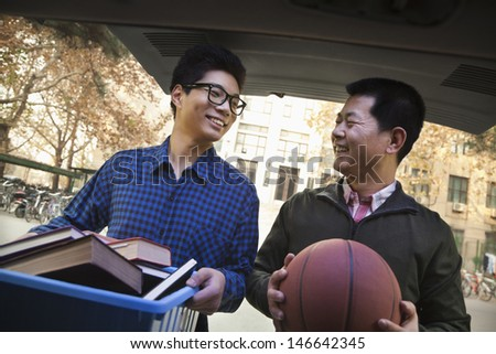 Father and Son in back of car in front of dormitory - stock photo