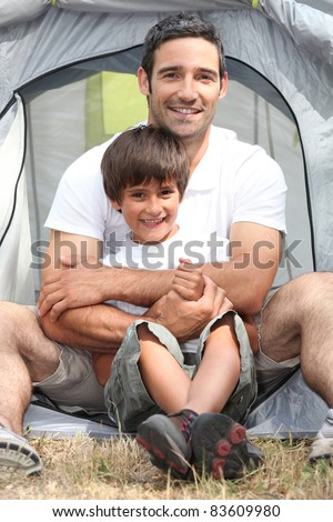 Father and son in front of their tent - stock photo