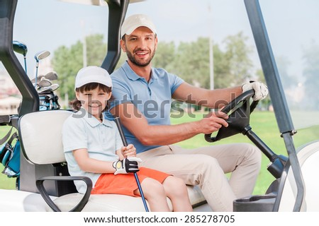 Father and son in golf cart. Smiling little boy sitting in golf cart while his father driving it - stock photo